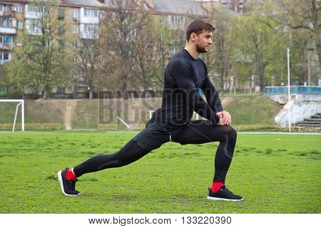 young attractive man athlete warming up at the stadium making stretching exercise - squats lungesin a black tracksuit
