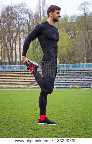 young attractive man athlete warming up at the stadium making stretching in a black tracksuit