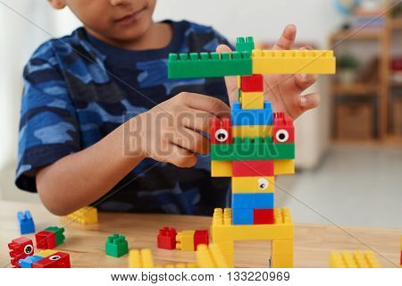 Boy playing with coloful cubes at the table