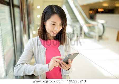 Woman use of mobile phone inside shopping mall