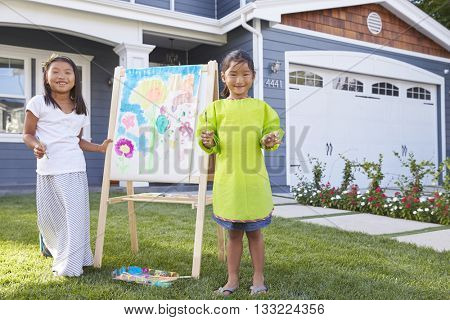 Portrait Of Two Girls Painting Picture In Garden