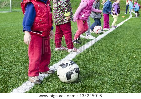 Kids playing together football on station with trainer