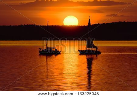 Yachts in the lake at sunset. Yachting tourism -  evening walk. Towing yacht during sunset  on the lake