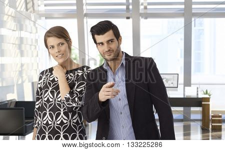 Young caucasian businessman and wife visiting bank office. Smiling, curious, pointing at something. Copyspace.