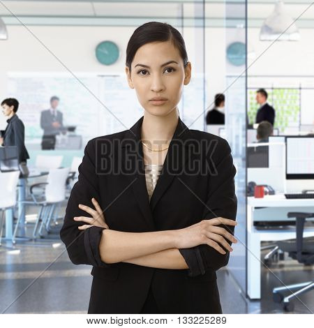 Serious young asian businesswoman at busy corporate office.
