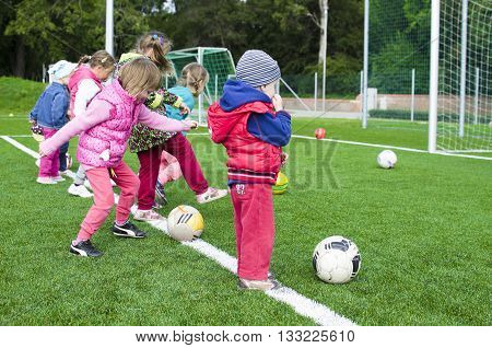 Kids shooting on football station in group