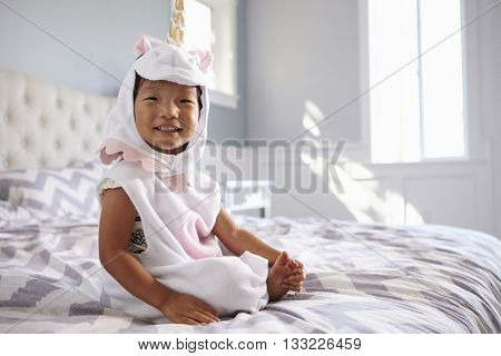Girl Dressed In Unicorn Costume Sitting On Bed At Home