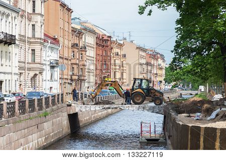 AINT PETERSBURG RUSSIA - MAY 25 2016: Repair of the bridge on the New Holland Island in downtown St. Petersburg. Works excavator and male workers