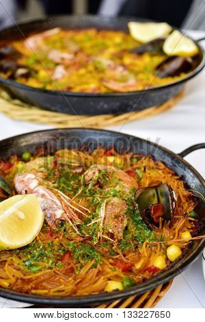closeup of a spanish fideua, a typical noodles casserole with seafood, in a paella pan on a set table and a paella in the background