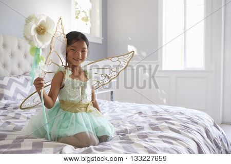 Girl Dressed In Fairy Costume Sitting On Bed At Home