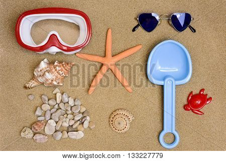 high-angle shot of some summer stuff, such a diving mask, a starfish, a pair of heart-shaped sunglasses, a toy shovel, some conchs and some pebbles, on the sand of a beach