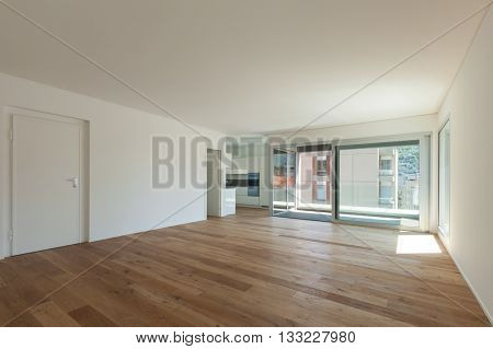 Interior of empty apartment, wide room with parquet floor and windows