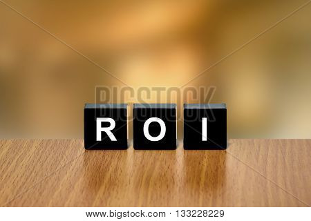 ROI or return on investment on black block with blurred background