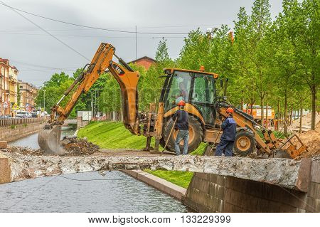 SAINT PETERSBURG, RUSSIA -  MAY 25, 2016: Repair of the bridge on the New Holland Island in downtown St. Petersburg. Works excavator and male worker