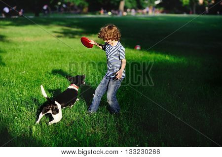The boy plays on a lawn with dog. Green field in the summer park. Blonde boy holding a red flying disc. The dexterous dog jumps up trying to grab a disk. Funny game.