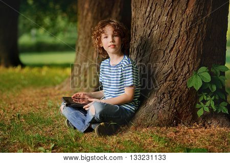 The boy of 8-9 years sits in park under a tree with the tablet in hands. The little fellow with a blond curly hair looks in a camera. In ears earphones. Behind the back there is a thick tree trunk.