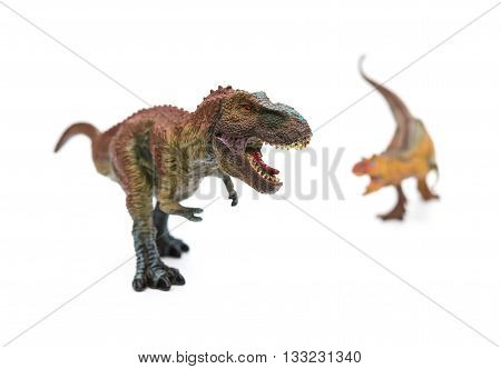 tyrannosaurus in front of carnotaurus on white selective focus
