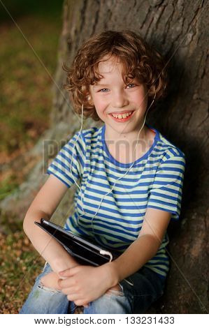 The cheerful boy sits under a tree with tablet on lap and puts out the tongue. The boy has wild fair hair and blue eyes. He with a smile looks in a chamber. Behind the back trunk of a big old tree.