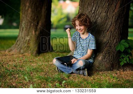 The boy of 8-9 years sits leaning against a tree and holds the tablet on a lap. In ears earphones. Jeans are torn on a lap He has a happy look. Gesture of his hand indicates pleasure.