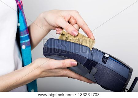 girl holding a POS terminal, customer is paying by credit card. electronic money and credit card terminal.