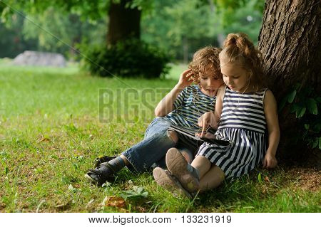 Boy and girl of 8-9 years sit on a grass in park with the small laptop. Children with interest look at the screen. They sit having extended legs having leaned against a thick tree trunk.