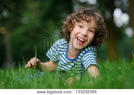 The boy of 8-9 years lies in a green grass and laughs. He has blond curly hair a turned-up nose and blue eyes. Playful and happy look. The boy cheerfully looks in a camera.