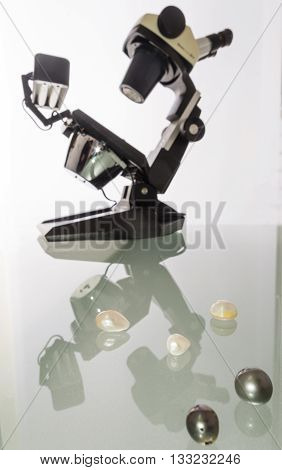 Microscope and collection of natural gems and pearls by the gemologist