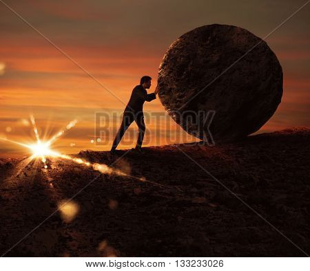 Man pushes a boulder uphill at sunset