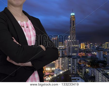 Single smart business woman wear black suit and crossed her arms stand on modern building background