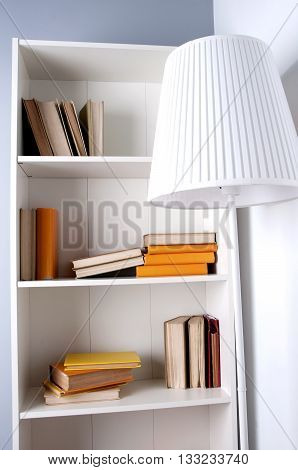 wood shelf with book. a bookcase with books from floor lamp. The interior of the office or at home