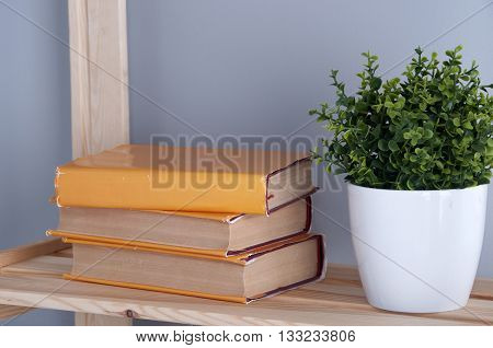 Stack of hardback books on wooden bookshelf. Back to school.
