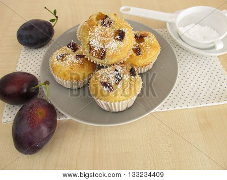 Homemade small muffins with plums and icing sugar