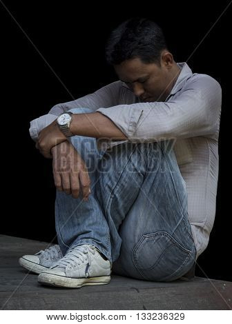 Portrait of lonely / disappointed / unhappy businessman sitting on wood floor in black background (Dark tone)