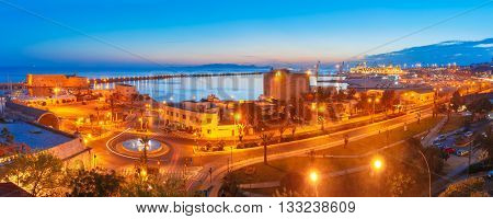 Aerial panoramic view of old harbour of Heraklion with Venetian Koules Fortress and marina during blue hour after sunset, Crete, Greece.