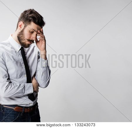 The young handsome man doubting over gray background