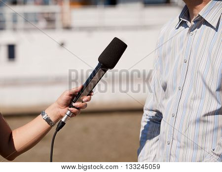 Journalist holding a microphone conducting an TV or radio interview