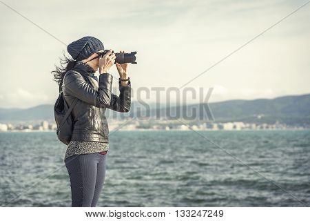 Girl photographer takes photos or videos on the camera on a background of a sea landscape.
