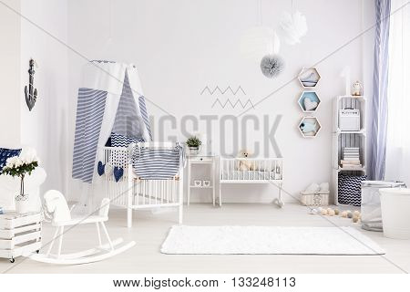 Beautiful, light baby room with white crib and stylish navy decorations