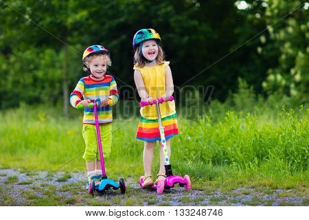 Little boy and girl in safety helmets with scooters. Child learning to ride a scooter in a park. Preschoolers riding a kick board. Kids play outdoors. Active leisure and outdoor sport for children.