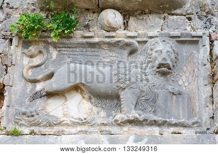 Fragment of stone wall of ruins of fortress of St. John (Illyrian fort) with image of lion Kotor Montenegro