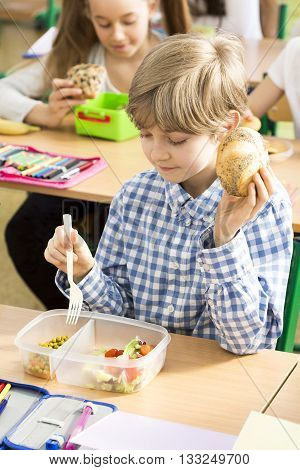 Cute little boy eating the healthy breakfast from his box during lunch break at school