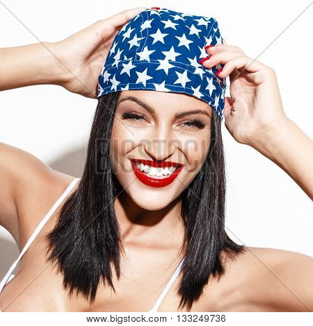 Happy woman with star headscarf and red lips laughing at white wall american lifestyle