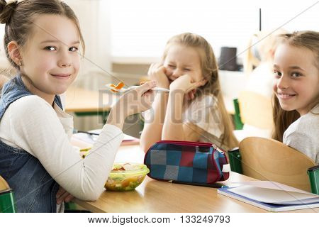Three little pretty girls eating together during lunch break. Sitting by one table in classroom