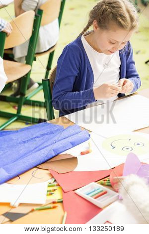 Cute little girl creating the picture during art classes. Using different techniques and materials