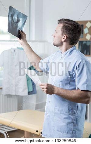 Male experienced physiotherapist checking the xray photo