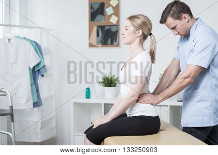 Young physiotherapist doing hard  lumbar spine mobilization
