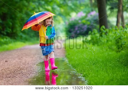 Little girl playing in rainy summer park. Child with colorful rainbow umbrella waterproof coat boots jumping in puddle and mud in the rain. Kid walking in autumn shower. Outdoor fun by any weather