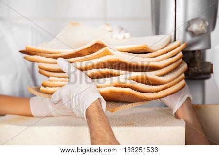 Baker's Hands Passing Unwanted Bread Slices
