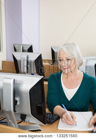 Confident Senior Woman Writing Notes In Computer Class