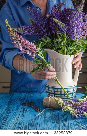 Woman's hands styling together a bouquet on blue table